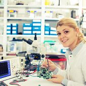 picture of microprocessor  - girl student studying electronic device with a microprocessor - JPG