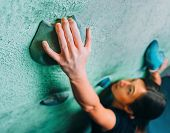 foto of climbing wall  - Young woman climbing up on wall in gym focus on hand - JPG