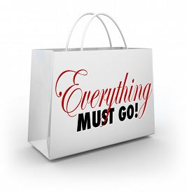 stock photo of going out business sale  - Everything Must Go words on a white shopping bag at a store holding a Going Out of Business sale to clear out its inventory - JPG