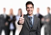 stock photo of thumb  - Smiling businessman giving thumbs up in front of his team - JPG