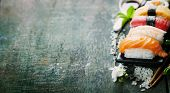 stock photo of chopsticks  - sushi with chopsticks on old  wooden background - JPG