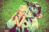 stock photo of meadows  - Happy little girl with her mastiff dog on a meadow in summer day - JPG
