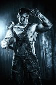 stock photo of mines  - Handsome muscular coal miner with a hammer over dark grunge background - JPG