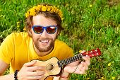pic of hippy  - Happy carefree young man sitting on a grass and playing his little guitar - JPG