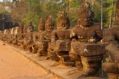 stock photo of demons  - Stone Asura demons hold the naga serpent king Vasuki on the bridge entrance to Angkor Thom Cambodia - JPG