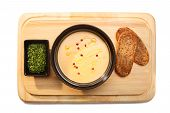 stock photo of condiment  - Hearty soup puree on a wooden plate served with sour green condiment and whole grain bread - JPG