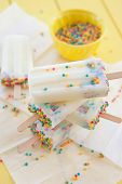 picture of popsicle  - Homemade frozen vanilla popsicles with colorful sprinkles - JPG