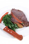 foto of kale  - grilled beef steak meat with red hot pepper and fresh raw kale leaf served on white plate isolated over white background - JPG