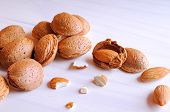picture of shells  - Group of almonds in shell and shelled on a white wooden table top view - JPG