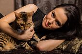 stock photo of bengal cat  - Young beautiful brunette holding a Bengal cat - JPG