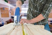 pic of sawing  - Carpenter cutting wooden plank with electric saw against workshop - JPG