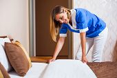 foto of maids  - Happy maid making bed in hotel room - JPG