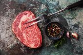picture of meats  - Raw fresh marbled meat Black Angus Steak and meat fork on metal background - JPG