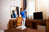 stock photo of maids  - Image of maid fixing the curtain in hotel room - JPG