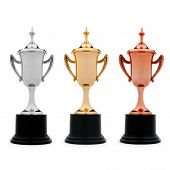 stock photo of plinth  - Three trophy cups in gold silver and bronze with plinths and lids isolated on a white background to be awarded to the first second and third places contestants in a competition - JPG