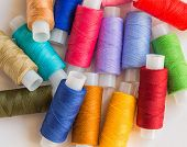 picture of rayon  - Colorful spools of thread pile on white background - JPG