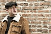 foto of newsboy  - Cool guy rocks an aviator jacket and newsboy cap as he takes a moment to think - JPG