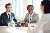 image of interview  - Smiling businessmen listening to young female during interview - JPG