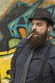 foto of pimp  - Snazzy bearded man smokes a cigarette on a city street - JPG