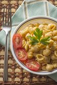 stock photo of italian parsley  - Delicious macaroni and cheddar cheese with fresh sliced grape tomatoes and parsley sprig - JPG