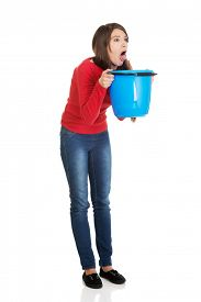 stock photo of vomiting  - Young sick woman vomiting to bucket - JPG