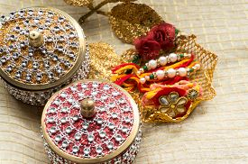 picture of rakhi  - Rakhi thread with decorated boxes on a golden cloth - JPG