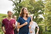 Mature woman running with group of people at park. Happy smiling woman with group of friends running poster