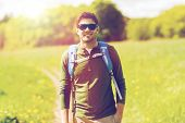 travel, hiking, backpacking, tourism and people concept - happy young man in sunglasses with backpac poster