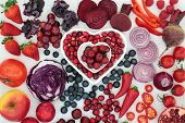 Purple and red health food with fruit and vegetables in heart shaped porcelain dishes and loose on d poster
