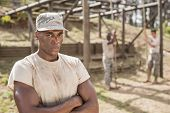Portrait of military man standing with arms crossed during obstacle course in boot camp poster
