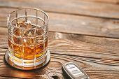Glass of whiskey or alcohol drink with ice cubes and car key on rustic wooden table with copy-space. poster