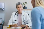 Senior female doctor listening to patient explaining her painful in her office. Mature woman doctor  poster