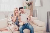 Young Beautiful Couple Of Blondie And Brunette Guy Are Watching Movie Under The Beige Plaid, Eating poster
