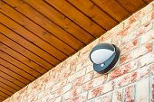 Modern Wall Lamp With Motion And Light Sensor On The Brick Wall poster