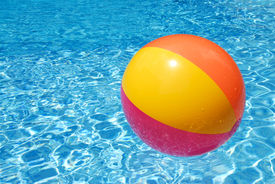 image of pool ball  - A colorful beach ball floating on the swimming pool - JPG