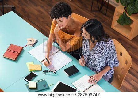 poster of Two young women studying in library together, preparing for exams. High angle view of brazilian stud