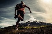 Young woman, trail running athlete runs on the trail with loose ground and volcano on the background poster
