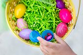 Close up view of an open plastic egg with Easter candy in it. A hand is pulling out candy out of the poster
