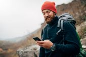 Young Bearded Man Smiling And Sending Messages For His Family From His Cellphone, During Hiking In M poster