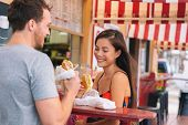 Happy couple eating sandwiches in typical retro cafe in Florida. Cuba sandwich local food. Summer tr poster