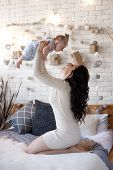 Young Mother Holding Her Newborn Child. Woman And New Born Boy Relax In A White Bedroom. A Young Mot poster