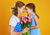 Happy Mothers Day! Child Daughter   Gives Mother A Bouquet Of Flowers On Color Yellow Background. poster