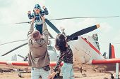 Flying Like A Bird. Woman And Man With Boy Child At Helicopter. Happy Family Vacation. Family Couple poster