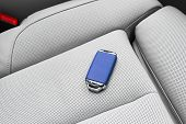 Closeup Inside Vehicle Of Wireless Blue Leather Key Ignition On White Leather Seat. Wireless Start E poster
