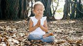Little Child Girl Meditating Alone Under Banyan Tree poster