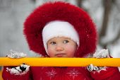 foto of ruddy-faced  - Little girl in a red jumpsuit and mittens - JPG