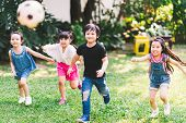 Asian And Mixed Race Happy Young Kids Running Playing Football Together In Garden. Multi-ethnic Chil poster