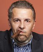 stock photo of hustler  - Man wearing suit gangster style smoking cigar - JPG