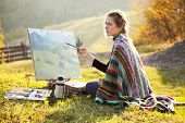 foto of draft  - Young artist painting an autumn landscape - JPG