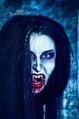 Close-up portrait of a bloodthirsty female vampire. poster